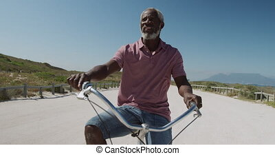 Senior man on a bike near the beach