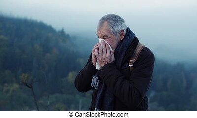 Senior man on a walk in autumn nature. - Active senior man...