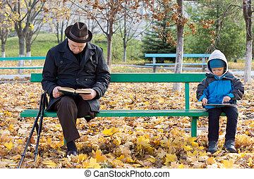 Senior man on crutches reading with his grandson