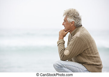 Senior Man On Holiday Kneeling On Winter Beach
