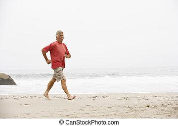 Senior Man On Holiday Running Along Winter Beach