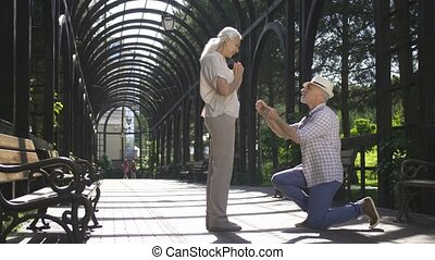 Senior man on knee proposing his woman to marry - Full...