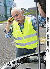 senior man on the phone looking at his broken car