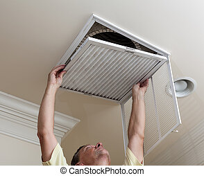 Senior man opening air conditioning filter in ceiling - ...