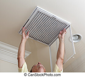 Senior man opening air conditioning filter in ceiling -...