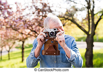 Senior man outside in spring nature taking pictures.