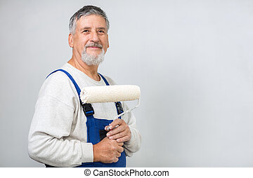 Senior man painting a wall