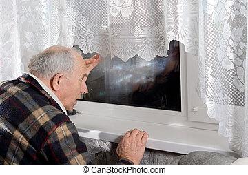 Senior man peering through a window at night