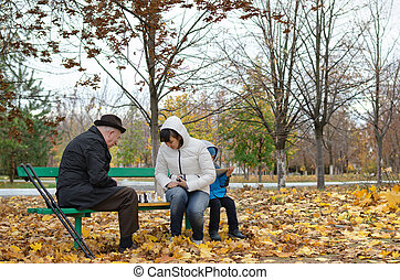 Senior man planning his next chess move sitting in park banch