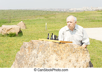 Senior man playing chess on a rock