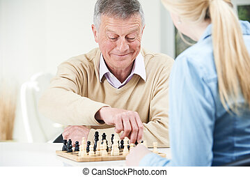 Senior Man Playing Chess With Teenage Granddaughter