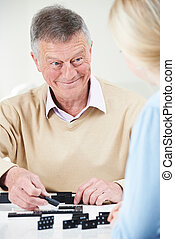 Senior Man Playing Dominoes With Teenage Granddaughter