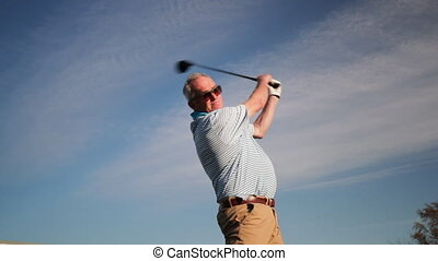 Senior Man Playing Golf - Low angle shot of a senior man...
