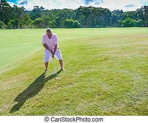 Senior man playing golf on a sunny day
