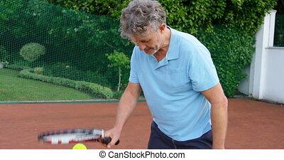 Senior man playing tennis in tennis court 4k - Close-up of...