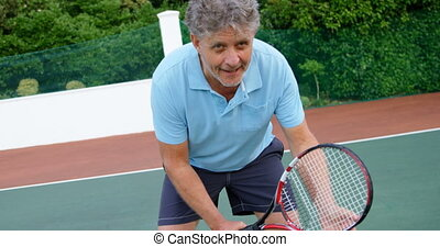 Senior man playing tennis in tennis court 4k - Close-up of...