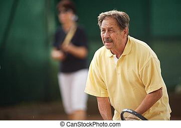 Senior man plays tennis - Active senior man in his 70s...