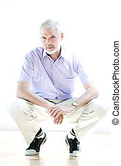 Senior man portrait squatting cheerful - caucasian senior ...