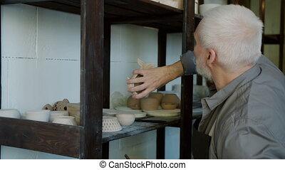Senior man potter doing inventory looking at ceramics and ...