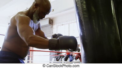 Senior man practicing boxing on the punching bag 4k - Senior...