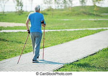 Senior Man Practicing Nordic Walking Back View