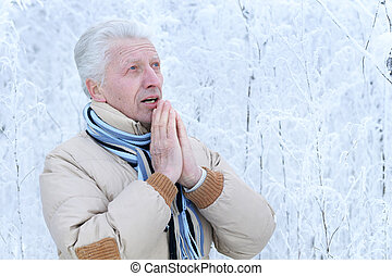 Senior man praying and posing in winter park - Portrait of ...