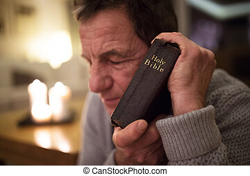 Senior man praying, holding Bible in his hands, eyes closed.