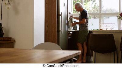 Senior man preparing coffee in kitchen 4k