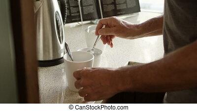 Senior man preparing coffee in kitchen at home 4k