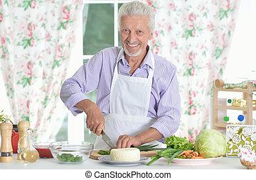 Senior man preparing dinner in kitchen
