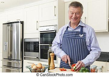 Senior Man Preparing Meal In Kitchen