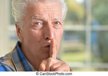 Senior man presses his finger on mouth