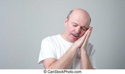 Senior man pretending sleeping on his hands and snoring