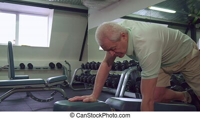 Senior man pulls dumbell up on the bench