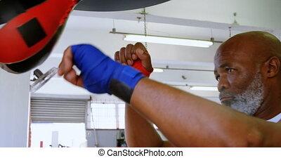 Senior man punching the speed bag in the fitness studio 4k