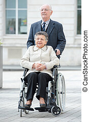 senior man pushes his disabled wife through the city
