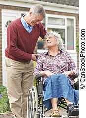Senior Man Pushing Disabled Wife In Wheelchair