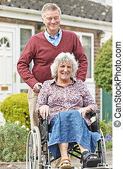 Senior Man Pushing Disabled Wife In Wheelchair