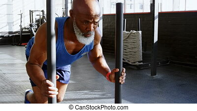 Senior man pushing weight sled in the fitness studio 4k -...