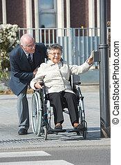 senior man pushing woman in wheelchair