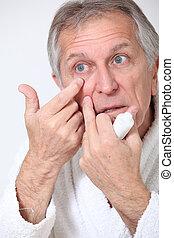 Senior man putting concealer around his eyes