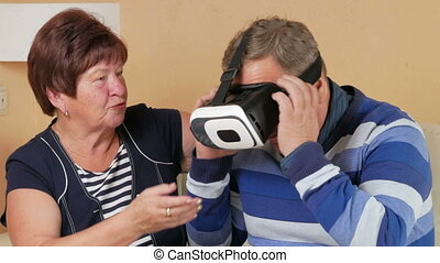 Senior man putting on glasses for the first time virtual reality together with a woman. The man swings his arms and shakes his head. The wife holds her husband's hand and looking carefully.
