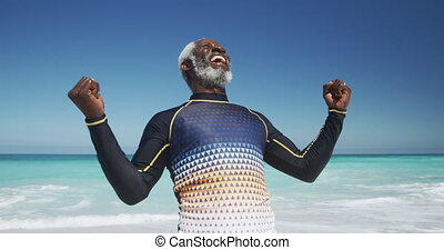 Senior man raising his arms at the beach - Front view of a ...