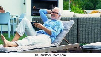 Senior man reading a book in garden 4k