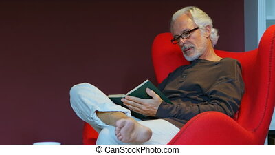 Senior man reading a book in living room 4k