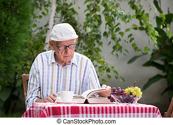 Senior man reading book in garden