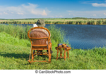 Senior man reading book while sitting in the wicker rocking-chair on a riverside
