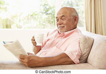 Senior Man Reading Book With Drink At Home