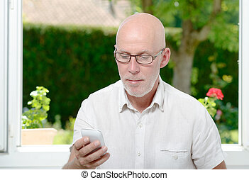 Senior man reading message on smartphone