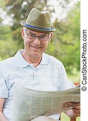 Senior man reading newspaper at par